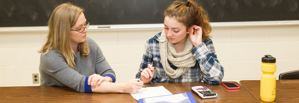teacher and student at a desk working