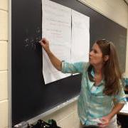 teacher writing on a chalkboard